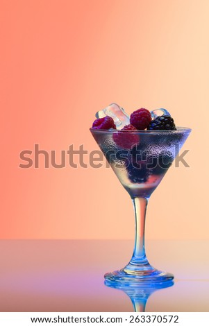 Refreshing raspberry and blackberry cocktail with ice, studio shot - stock photo