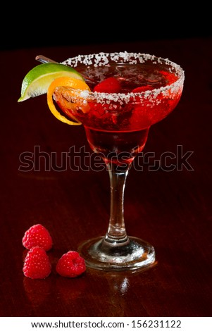 refreshing raspberry margarita isolated dark bar garnished with a lime wedge and an orange twist - stock photo