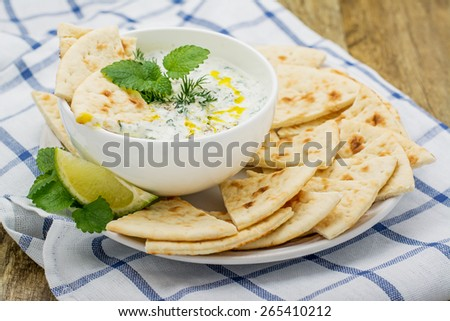 Refreshing sauce based on Greek yogurt, cucumber, dill, garlic, salt and butter as a sauce for vegetables, meat bread on a wooden background. selective Focus - stock photo