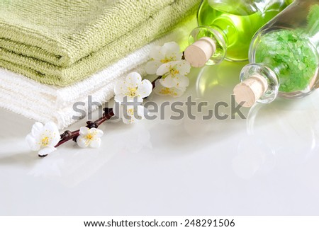 Refreshing spring spa set with scented sea salt and essential oil for massage or aroma therapy decorated with apricot flowers - stock photo