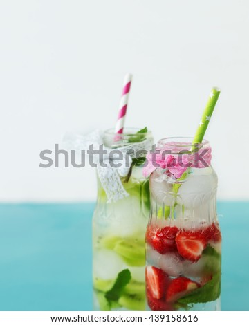 Refreshing summer drink with juicy fruit and fresh mint in a vintage glass bottles closeup. Ingredients for the preparation of cocktails on the background.  - stock photo