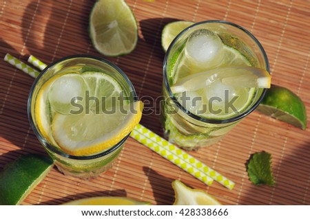 Refreshing summer drink with lemon, lime, mint and ice in glasses, top view - stock photo