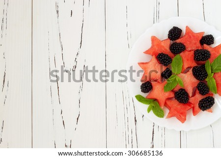 Refreshing watermelon salad with blackberries and mint. Fresh star shaped watermelon. Copy space background - stock photo