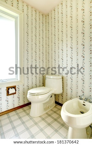 Refreshing white bathroom with window. View of white toilet and bidet