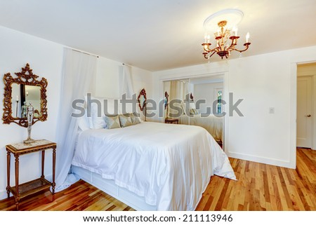 Refreshing white bedroom with beautiful bed and antique nightstand