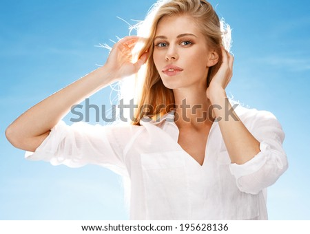 Refreshment on a hot day / portrait of happy girl making hairdo on blue background
