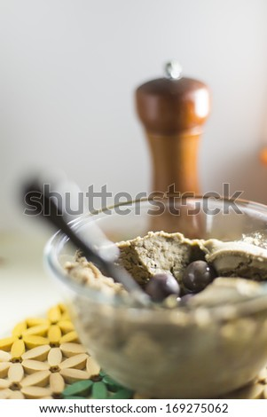 Refried beans in glass bowl with black olives & pepper grinder