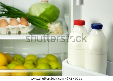 Refrigerator full with some kinds of food - fruits, vegetable, eggs and milk - stock photo