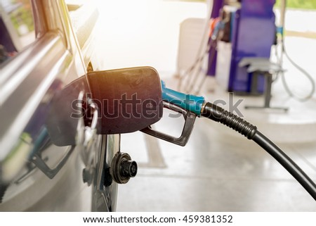 Refuel at petrol pumps with fuel nozzle blue with bright sunlight