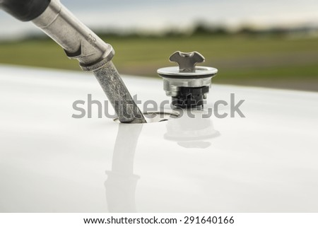 Refueling aircraft, fuel filler pipe, refueling jet fuel in an aircraft wing, Focused on refueling gun. Focused on refueling gun  - stock photo