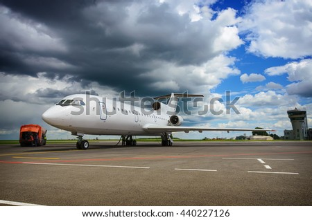 Refueling an airplane at the small russian airport against blue cloudy sky. Soft selective focus and shallow depth of field - stock photo