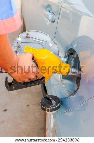 refueling with nozzle in car at gas station - stock photo