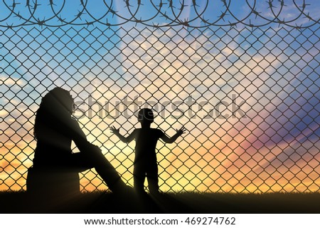 Refugees concept. Mother with a small child refugees, near the fence of barbed wire