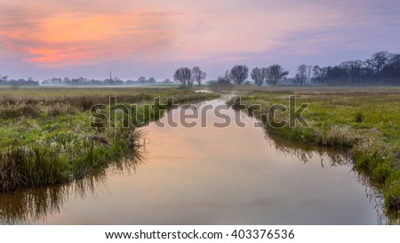 Regge river, Twente Netherlands. A meander forms when moving water in a stream erodes the outer banks and widens its valley, and the inner part of the river has less energy and deposits silt. - stock photo