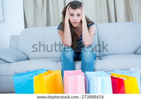 Regretful woman looking at many shopping bags at home in the living room - stock photo