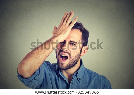 Regrets wrong doing.. Closeup portrait silly young man, slapping hand on head having a duh moment isolated on gray background. Negative human emotion facial expression feeling, body language, reaction - stock photo