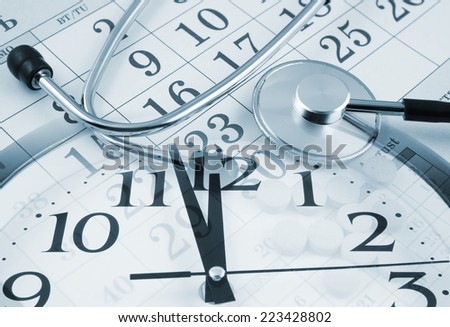 Regular medical examination concept, stethoscope on calendar and clock  - stock photo