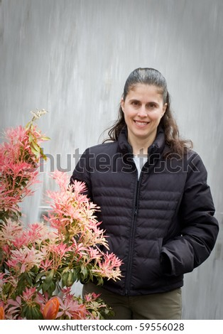Regular ordinary gal stands by flowers in front of neutral background - stock photo