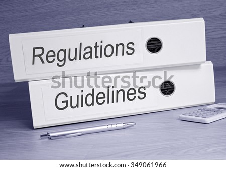 Regulations and Guidelines - two binders with text on desk in the office
