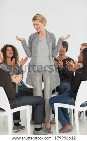 Rehab group applauding smiling woman standing up at therapy session - stock photo