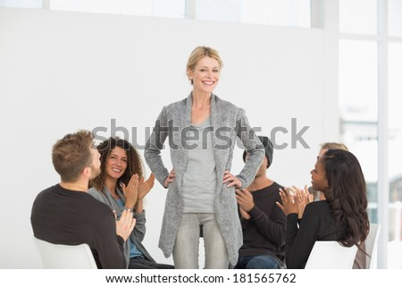 Rehab group applauding woman standing up at therapy session - stock photo
