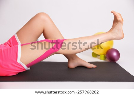 Rehabilitation after knee injury with kinesio tape - stock photo