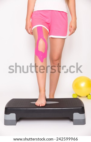 Rehabilitation after knee injury with kinesiology tape - stock photo