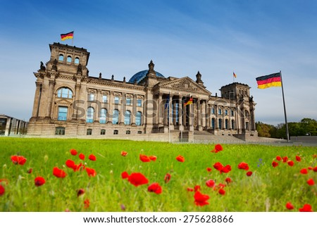 Reichstag view with red tulips in front and German flags in Berlin, Germany - stock photo