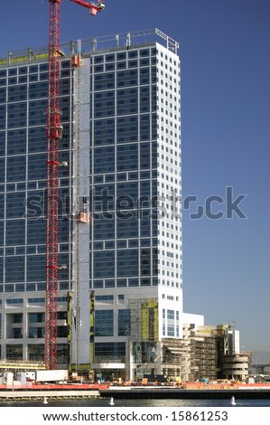 Reinforced steel & concrete building under construction. Safety guard rails, flyforms and tower crane