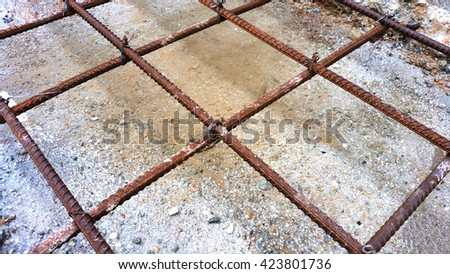 Reinforcement bars are secured to prevent displacement during concrete placement using tie wires. A close-up view shows tying reinforcing steel bars using quadruple-strand single tie  method. - stock photo