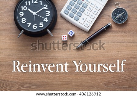 Reinvent yourself written on wooden table with clock,dice,calculator pen and compass - stock photo