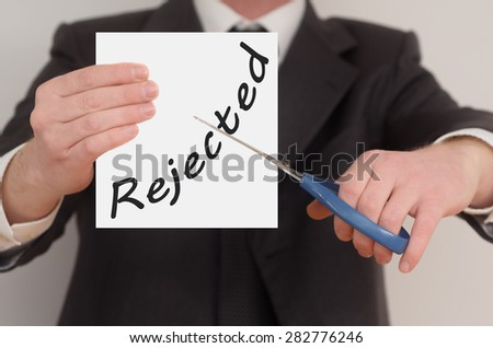 Rejected, man in suit cutting text on paper with scissors