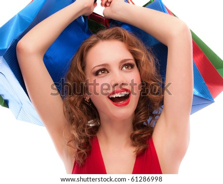 Rejoicing girl in red dress with purchases, isolated on white background. - stock photo