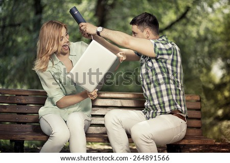 Relationship and arque concept. Yong playful couple with book and computer sitting in the park and jokingly argue. - stock photo