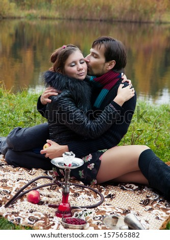 relationship between man and a woman at a picnic with a hookah - stock photo