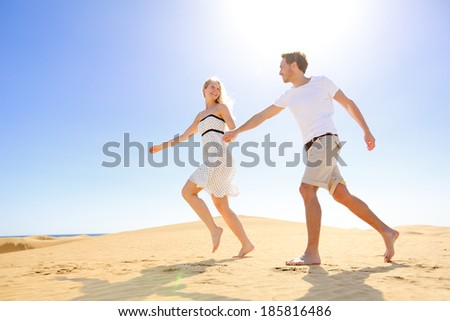 Relationship - happy couple playful romantic having fun under sun and blue sky in desert. Two young lovers running cheerful together on romance in summer. Cheerful Caucasian man and woman. - stock photo