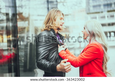 Relationship issues - Woman grabbing her boyfriend and shouting out loud - Girlfriends pushing her man and he tries to exculpate - stock photo