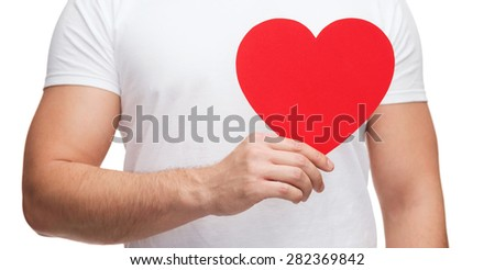 relationships and love concept - closeup of man hands with heart - stock photo