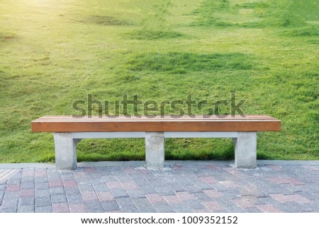 Relax and take a rest concept. Wood chesterfield with bricks floor and green grass in park or garden. Advertising background.  Picture for add text message. Backdrop for design art work.