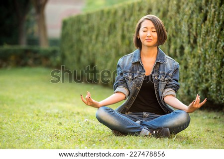 Relax. Beautiful smiling asian female student is sitting on the grass near the college. - stock photo