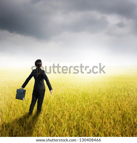 Relax business woman holding bag in yellow rice field and rainclouds - stock photo