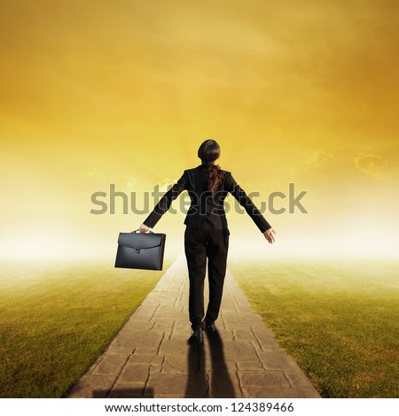 Relax business woman holding bag on Concrete road in Grass fields and sunset