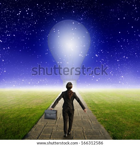 Relax business woman holding bag on Concrete road to Big idea bulb in Grass fields and star night