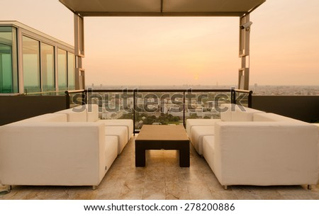 Relax coner on condominium roof top with sofa and table. - stock photo