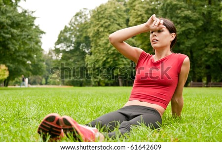 Relax in grass - tired woman after sport - stock photo