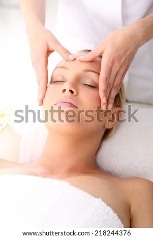 Relax in the spa - woman at face massage .Beautician beautiful woman massaging her temples . Woman in a beauty salon. Masseur massaging a woman in a spa. - stock photo