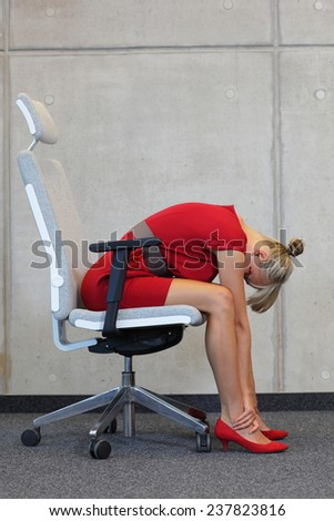relax on armchair in office - business woman in red dress  exercising - stock photo