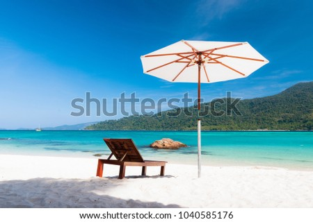 Relax on beautiful beach. Woodden chairs on sandy beach near the sea and mountain. Summer holiday and vacation concept for travel destination. Summer on the beach.