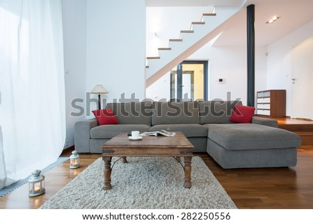 Relax space with big comfortable couch and wooden coffee table - stock photo
