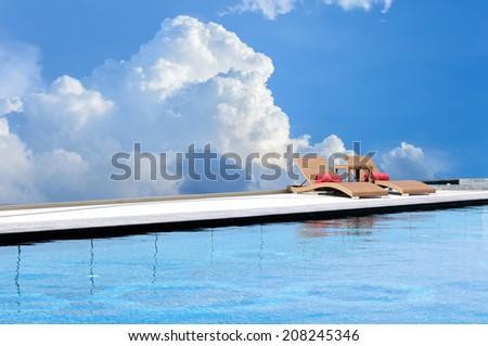 Relax Sun-beds near a swimming pool sky and cloud background - stock photo